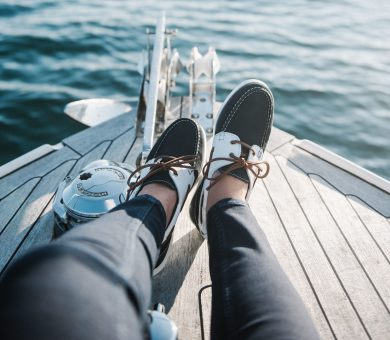 A person's feet on the boat sailing on the sea during daytime